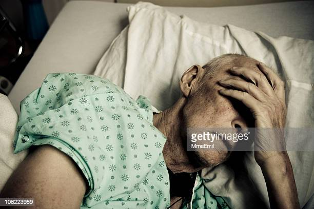 Sick and Senior Man Wearing Hospitable Gown Lying in Bed
