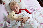The little boy is sick. He lies in bed. Red scarf is on his neck. Teddy Bear is in his hand.