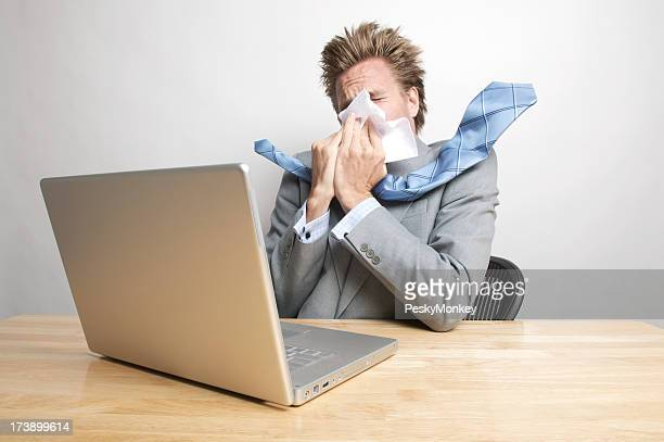 Sick Businessman Blowing His Nose Sitting at Office Desk