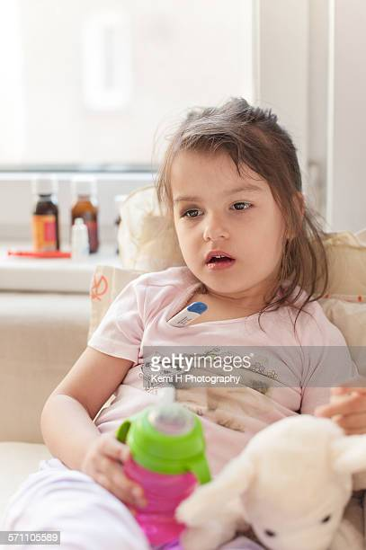 Sick child girl lying in bed with a fever, resting