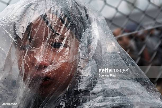 A sick child waits as his father pleads with the authorities to let him into a gate to see a doctor at the migrant processing center at the...