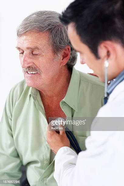Sick elderly man being examined by a male doctor