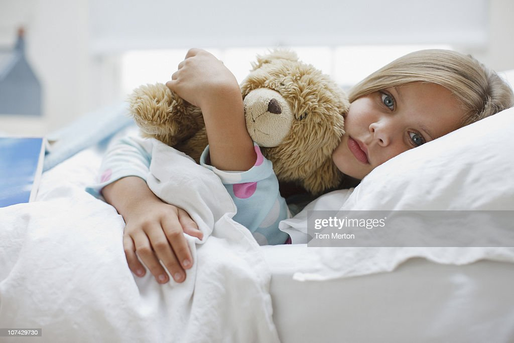 Sick girl laying in bed with teddy bear : Stock Photo