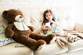 Cute little girl with thermometer and tissue paper sitting on sofa with doctor teddy bear with stethoscope in living room