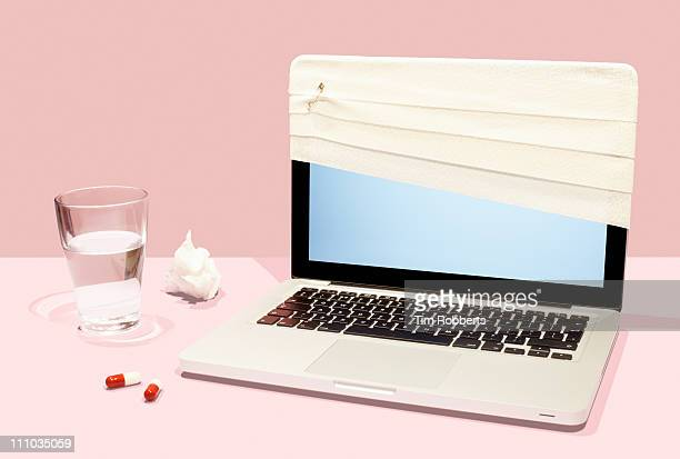 Sick laptop with bandage and pills.