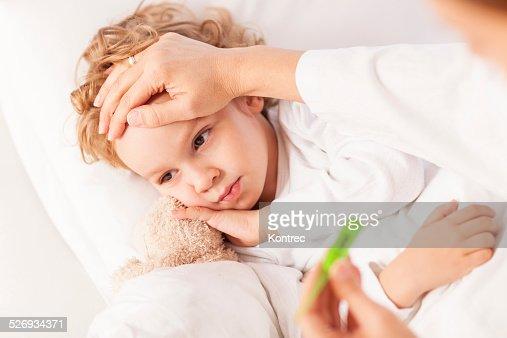 Sick little boy having his body temperature measured
