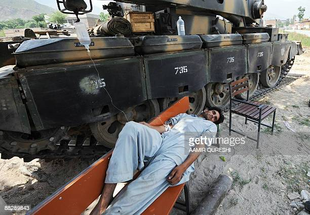 A sick local resident receives medical treatment while lying on a bench alongside an armoured vehicle in the village of Pir Baba in troubled Buner...