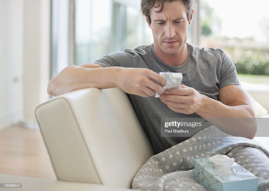 Sick man checking medicine package : Stock Photo