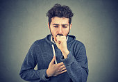 Young man having asthma problems and coughing badly covering mouth and holding hand on chest.