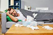 Sick man lying on sofa and sleeping at home