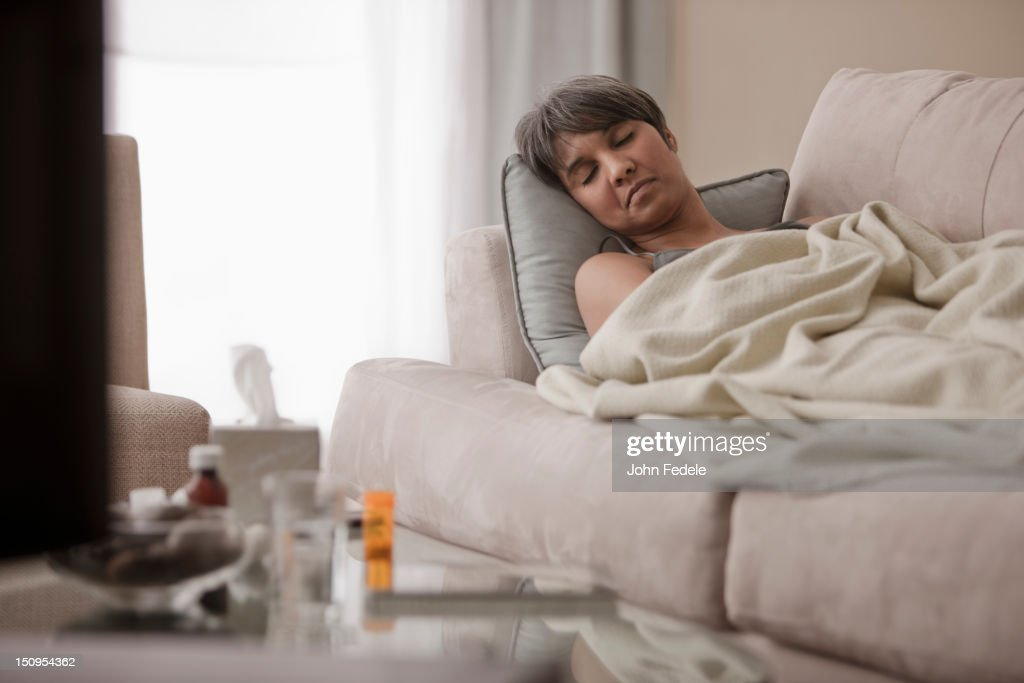 Sick mixed race woman laying on sofa