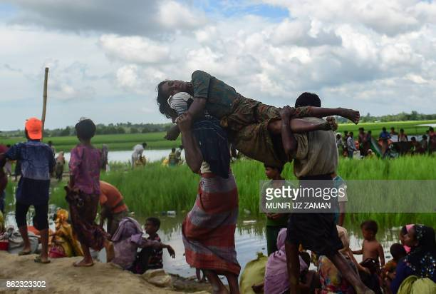 A sick Rohingya refugee woman is carried by two men in an area near no man's land on the Bangladesh side of the border with Myanmar after crossing...