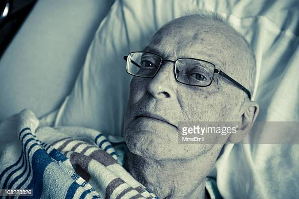 Sick, Senior Man Lying in Hospital Bed