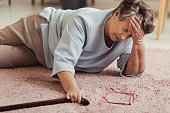 Sick senior woman with headache lying on the floor with wooden stick