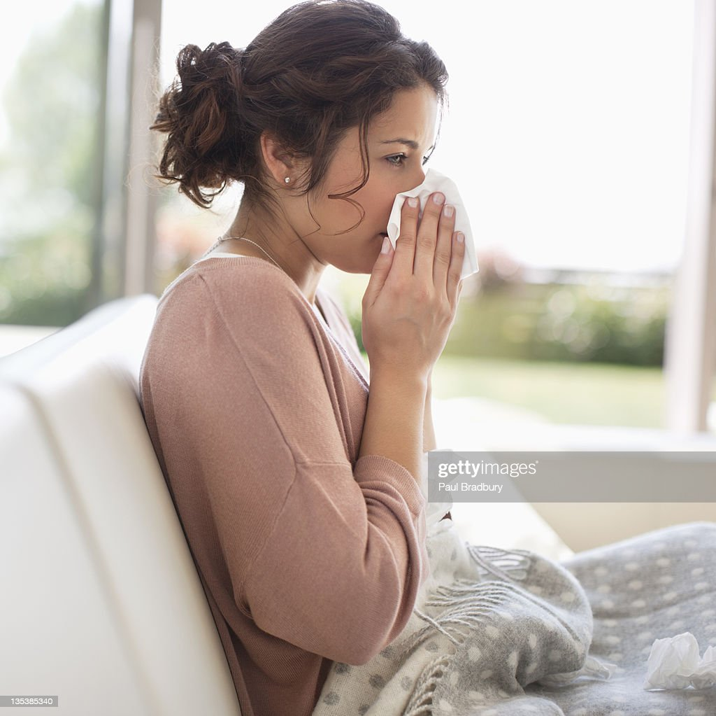 Sick woman blowing her nose : Stock Photo