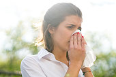 Sick woman blowing his nose into tissue, outdoors