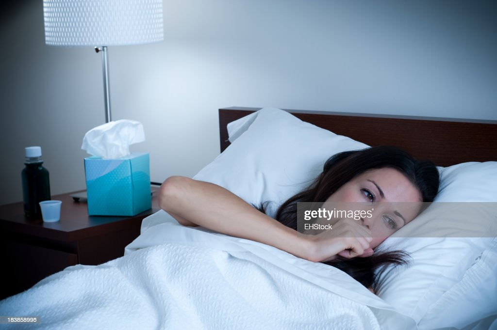 Sick Woman Coughing in Bed