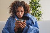 Black woman drinking hot tea and feeling comfortable