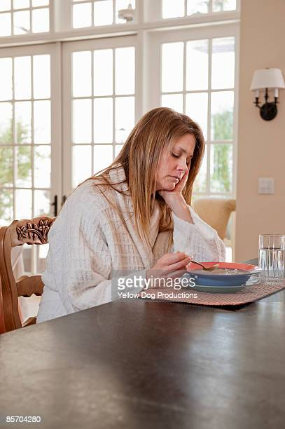 Sick Woman Having Soup at Kitchen Counter