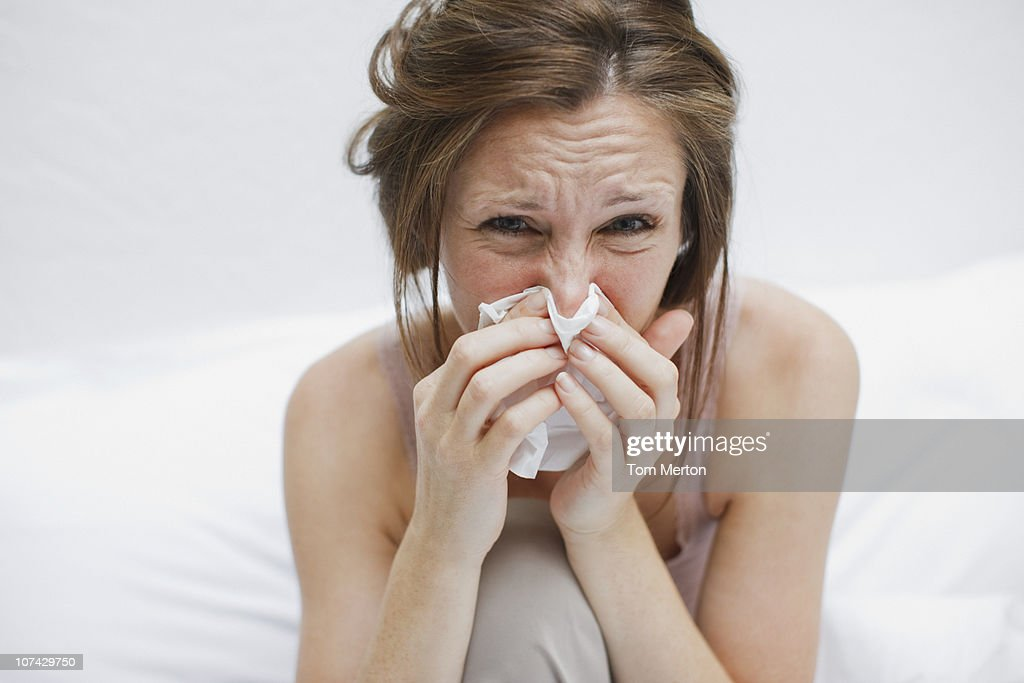 Sick woman in bed blowing nose : Stock Photo