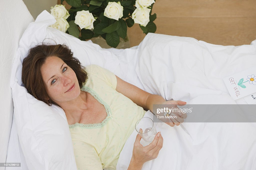Sick woman laying in bed and taking pills with water : Stock Photo