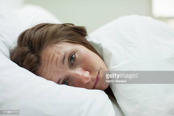 Kranke Frau im Bett unter Decke Bauchlage
