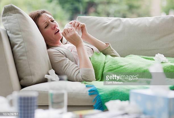 Kranke Frau Leg dich auf die Couch Schnäuzen