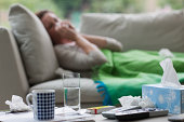 Sick woman laying on sofa blowing nose