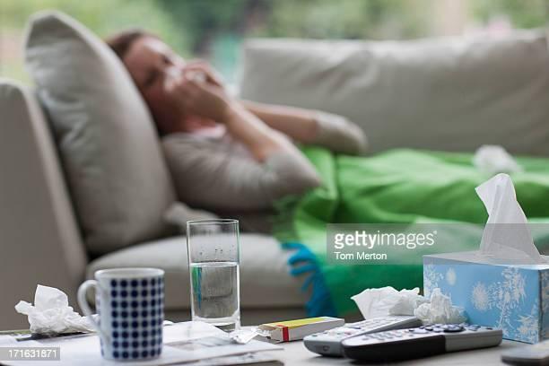 Mulher doente no sofá Assoar o Nariz poedeiras