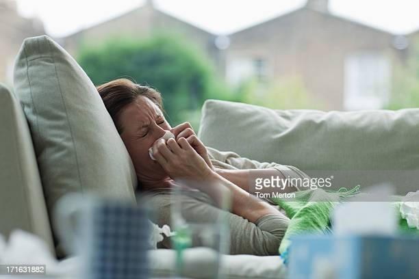 Femme malade allongé sur un canapé Se moucher