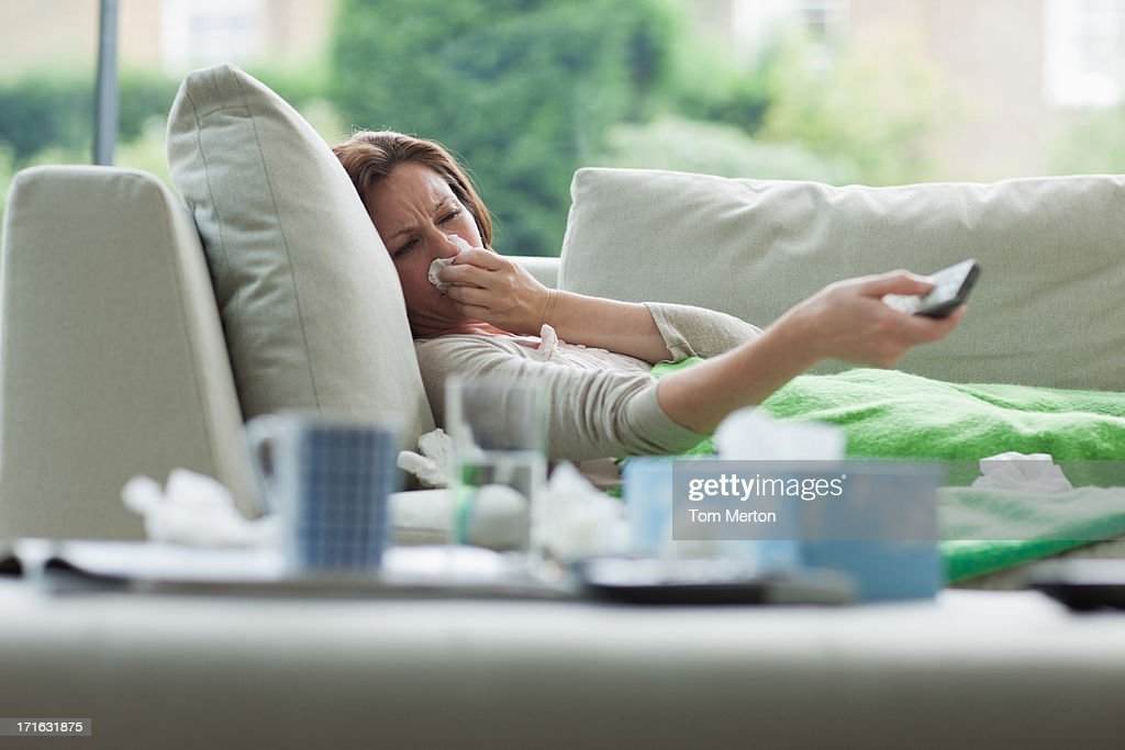 Sick woman laying on sofa holding remote control