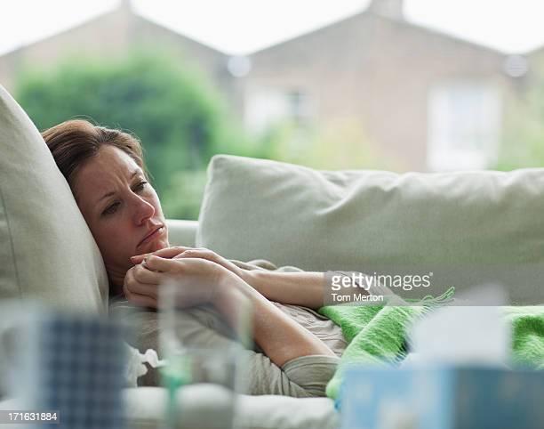 Femme malade allongé sur un canapé
