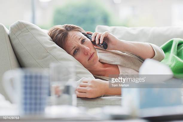 Sick woman laying on sofa talking on telephone