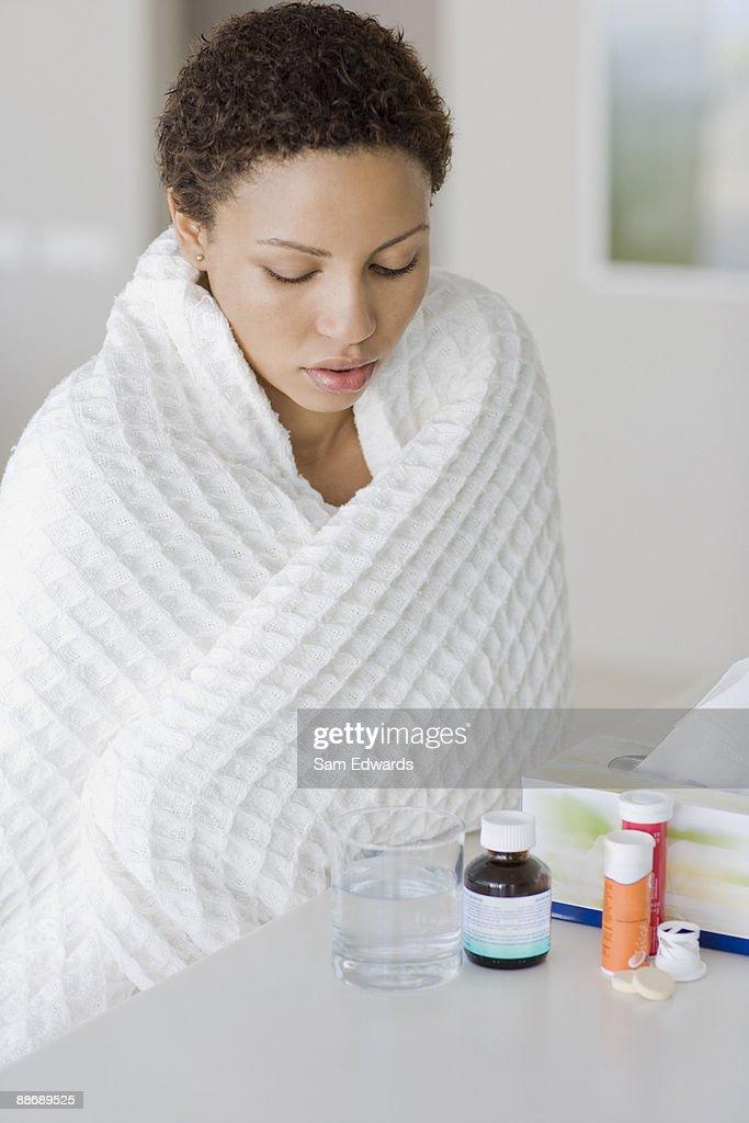 Sick woman looking at medication : Stock Photo