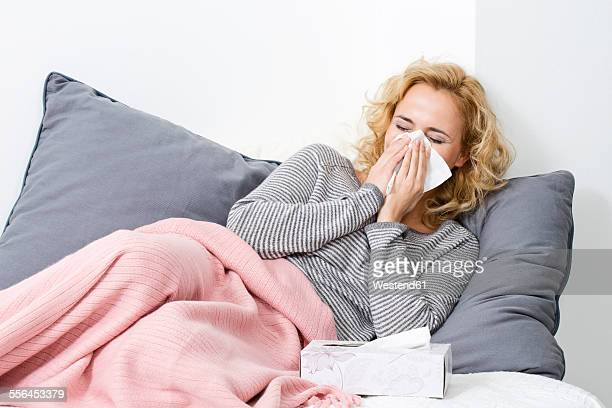 Sick woman lying on couch blowing her nose