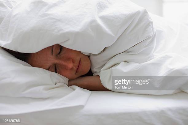 Sick woman sleeping in bed under blanket