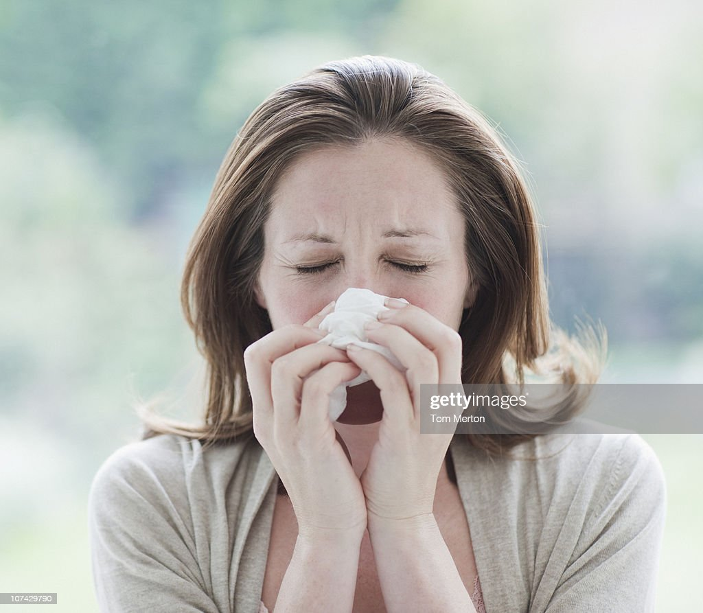 Sick woman wiping her nose : Stock Photo