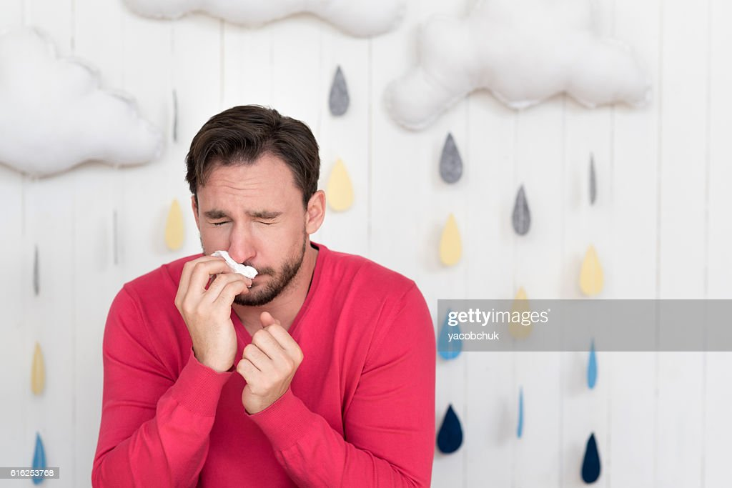 Sick young man sneezing : Foto de stock