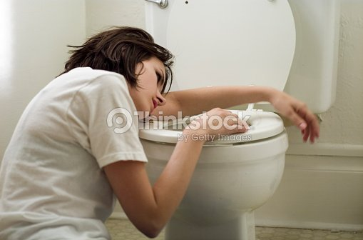 Sick Young Woman Leaning On Toilet Bowl Stock Photo