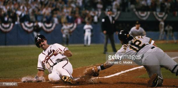 Sid Bream of the Atlanta Braves scores the winning run as Mike LaValliere of the Pittsburgh Pirates misses the tag during the Game 7 of the National...