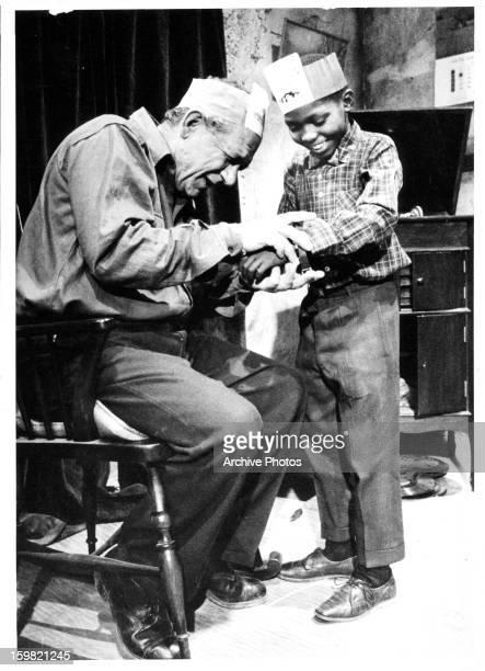 Sid James placing bracelet on Saul Pelle in a scene from the film 'Tokoloshe' 1965