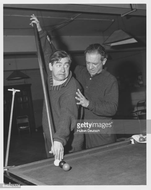 Sid James the British comic actor instructs fellow comedian Tony Hancock how to escape a snooker