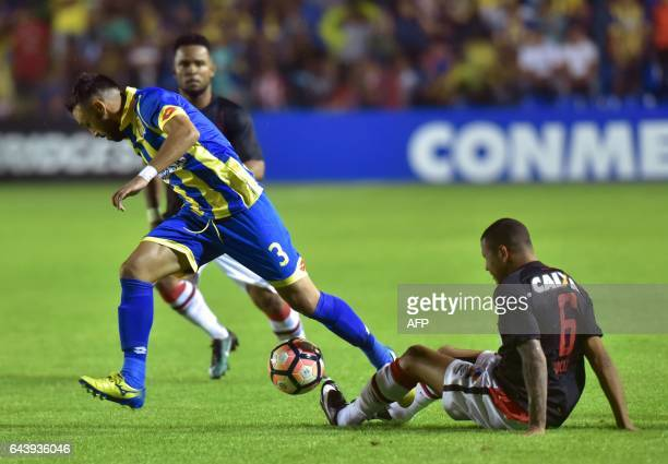 Sidcley of Brazil's Atletico Paranaense struggles for the ball with Gustavo Noguera of Paraguay's Deportivo Capiata during their Libertadores Cup...