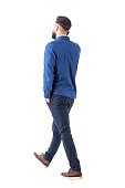 Side back view of young smart casual business man talk on the cellphone walking away. Full body isolated on white background.