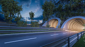 Digitally generated image of concrete tunnels with empty asphalt roads under a dramatic sky