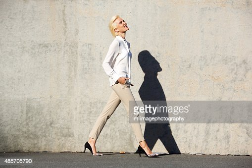 Side portrait of a cheerful young woman walking outside : Stock Photo