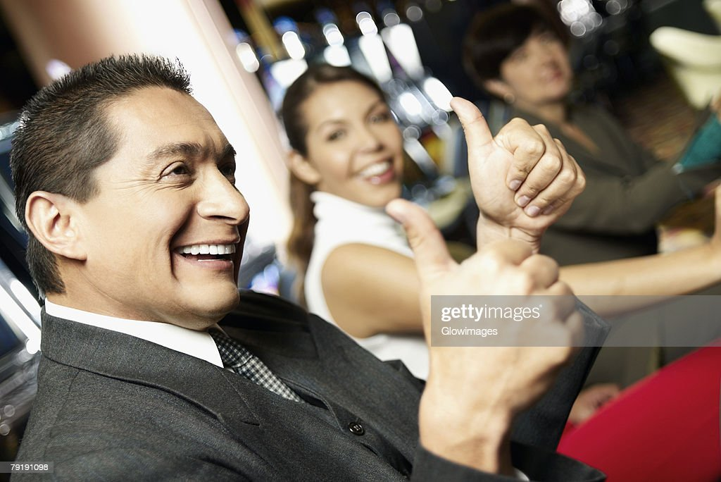 Side profile a mature man showing a thumbs up sign with his daughter beside him at a casino : Stock Photo