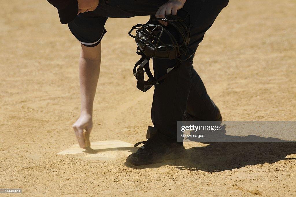 Side profile of a baseball umpire marking a baseball field