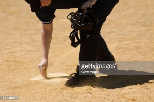 Side profile of a baseball umpire marking a baseball field