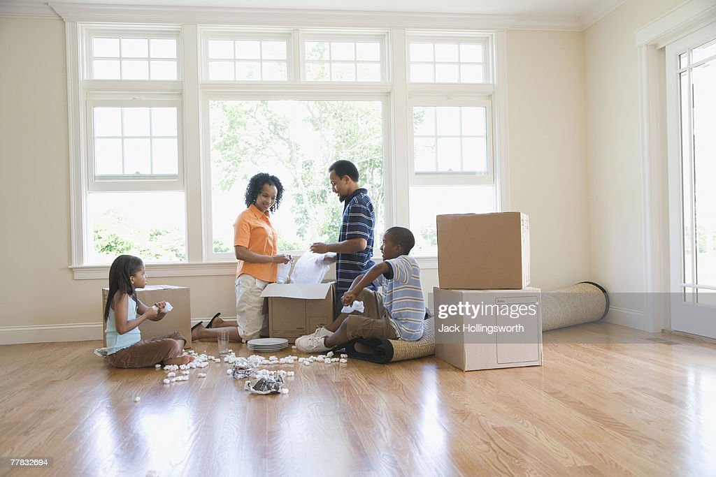 Side profile of a boy and a girl unpacking a cardboard box with their parents